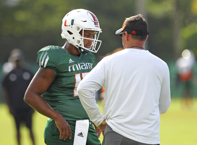 Miami Hurricanes offensive coordinator / quarterbacks Dan Enos talks with Hurricanes quarterback Jarren Williams throws during practice at the University of Miami Greentree Practice Field in Coral Gables on Wednesday, September 11, 2019 in preparation for their home opener against Bethune-Cookman Wildcats on Saturday at Hard Rock Stadium.(David Santiago/Miami Herald via AP)