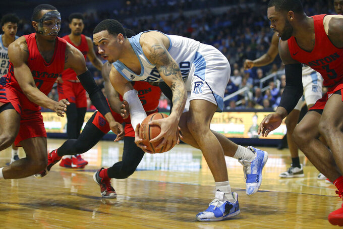 Rhode Island's Tyrese Martin (4) grabs a loose ball ahead of Dayton's Rodney Chatman (0) during the second half of an NCAA college basketball game Wednesday, March 4, 2020, in Kingston, R.I. (AP Photo/Stew Milne)