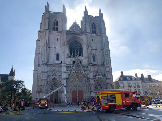 FILE - In this July 18, 2020, file photo, fire fighters brigade work to extinguish the blaze at the Gothic St. Peter and St. Paul Cathedral, in Nantes, western France. French authorities detained and charged a repentant church volunteer Sunday, July 26, 2020 after he told investigators that he was responsible for an arson attack that badly damaged a 15th-century Gothic cathedral. (AP Photo/Laetitia Notarianni, File)