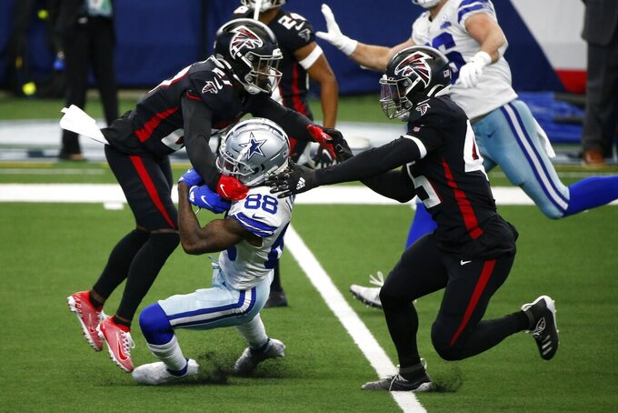 Atlanta Falcons strong safety Damontae Kazee, left, and linebacker Deion Jones, right, combine to stop Dallas Cowboys wide receiver CeeDee Lamb (88) from gaining yardage after a catch in the second half of an NFL football game in Arlington, Texas, Sunday, Sept. 20, 2020. (AP Photo/Michael Ainsworth)
