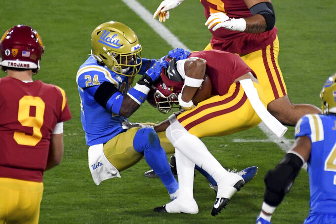 """FILE - In this Dec. 12, 2020, file photo, UCLA defensive back Qwuantrezz Knight (24) tackles Southern California wide receiver Gary Bryant Jr. (1) in the first half of an NCAA college football game, in Pasadena, Calif. """"People are expecting big things out of the Bruins,"""" Knight said. """"We just want to elevate all around and be the best that we can be. We are going to attack the season like that."""" (Keith Birmingham/The Orange County Register via AP, File)/The Orange County Register via AP)"""