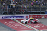 A.J. Allemdinger takes the checker flag to win the NASCAR Xfinity Cup Series auto race at Michigan International Speedway, Saturday, Aug. 21, 2021, in Brooklyn, Mich. (AP Photo/Carlos Osorio)