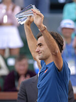 Roger Federer, of Switzerland, raises a trophy as he gestures toward fans after losing to Dominic Thiem, of Austria, in the men's final at the BNP Paribas Open tennis tournament Sunday, March 17, 2019, in Indian Wells, Calif. Thiem won 3-6, 6-3, 7-5. (AP Photo/Mark J. Terrill)