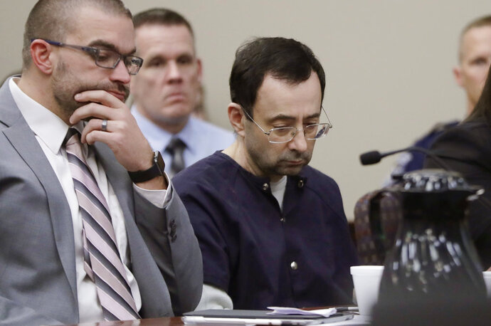 Larry Nassar sits with attorney Matt Newburg during his sentencing hearing Wednesday, Jan. 24, 2018, in Lansing, Mich. The former sports doctor who admitted molesting some of the nation's top gymnasts for years was sentenced Wednesday to 40 to 175 years in prison as the judge declared: