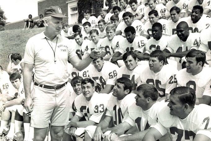 This Sept. 1, 1969, photo shows Maryland football coach Roy Lester greeting Maryland NCAA college football players on picture day in College Park, Md. Lester, who sandwiched a disappointing three-year stint as Terrapins coach between a highly successful career at the high school level, has died at the age of 96. His daughter, Amy Lester Greco, says her father died Sunday, May 3, ,3030, in Rockville, Maryland, due to complications from the new coronavirus. (Paul Hutchins/The Baltimore Sun via AP)