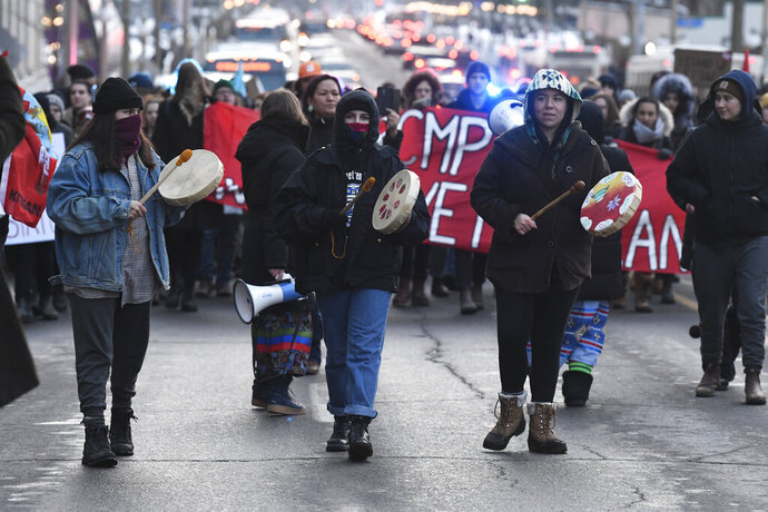 Protesters march on a street in Ottawa, Ontario, Wednesday, Feb. 12, 2020. The protesters are standing in solidarity with the Wet'suwet'en hereditary chiefs opposed to a Canada gas pipeline in northern British Columbia. (Adrian Wyld/The Canadian Press via AP)