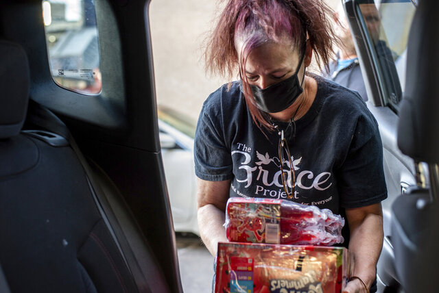 Megan Cohen's mom, Jennifer Shablin, a volunteer with The Grace Project, unloads juice donations from the back of her daughter's car parked outside The Last Stop in the Kensington neighborhood of Philadelphia on Thursday, Oct. 8, 2020. (Michele Haddon/Bucks County Courier Times via AP)