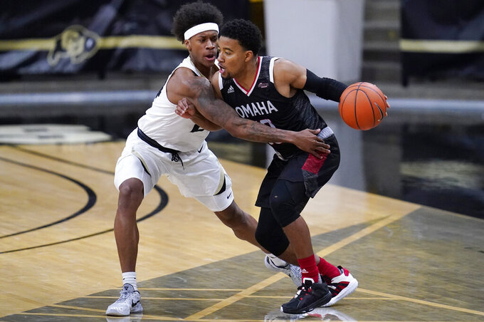 Colorado guard Eli Parquet, left, defends as Omaha guard Ayo Akinwole drives the lane in the second half of an NCAA college basketball game Wednesday, Dec. 16, 2020, in Boulder, Colo. Colorado won 91-49. (AP Photo/David Zalubowski)