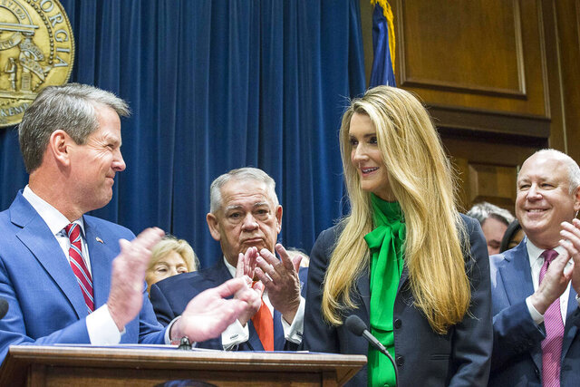 Businesswoman Kelly Loeffler, right, smiles while being introduced by Georgia Gov. Brian Kem, left,  as his pick to fill Georgia's vacant U.S. Senate seat at the Georgia State Capitol on Wednesday, Nov. 4, 2019, in Atlanta. (Alyssa Pointer/Atlanta Journal-Constitution via AP)