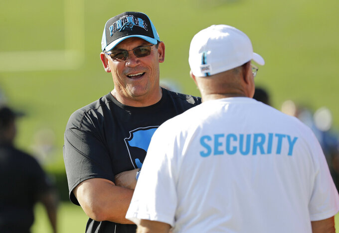 Carolina Panthers head coach Ron Rivera, left, talks with team owner David Tepper during practice at the NFL football team's training camp in Spartanburg, N.C., Thursday, July 25, 2019. (AP Photo/Chuck Burton)