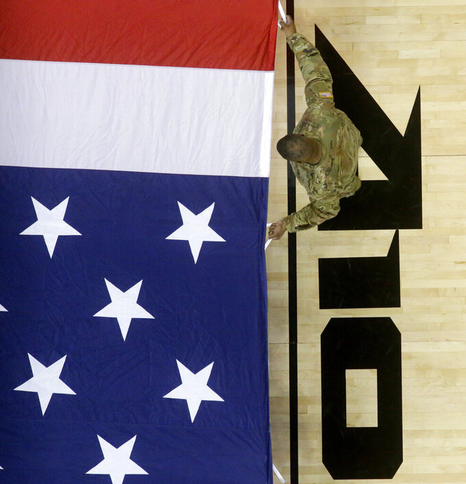 A United States serviceman holds a large flag during rehearsals prior to an NCAA college basketball final game between Saint Louis and St. Bonaventure in the Atlantic 10 men's tournament, Sunday, March 17, 2019, in New York. (AP Photo/Julio Cortez)