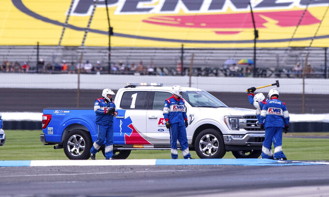 Members of the track crew work to repair a curb at Turn 5 during a NASCAR Cup Series auto race at Indianapolis Motor Speedway, Sunday, Aug. 15, 2021, in Indianapolis. (AP Photo/Doug McSchooler)