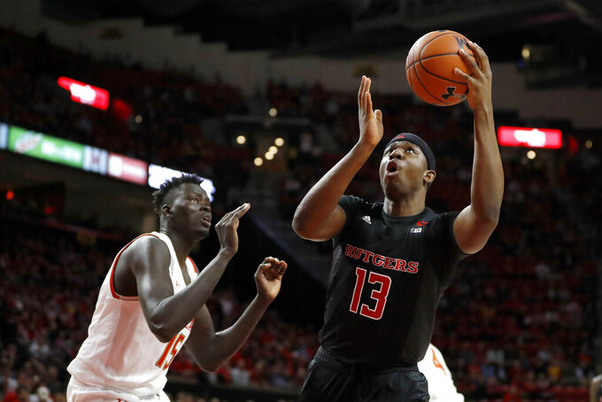 Rutgers forward Shaq Carter (13) goes up for a shot next to Maryland center Chol Marial (15) during the first half of an NCAA college basketball game, Tuesday, Feb. 4, 2020, in College Park, Md. (AP Photo/Julio Cortez)