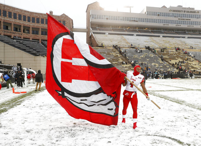 Utah running back TJ Green waves a school flag after an NCAA college football game against Colorado, Saturday, Nov. 17, 2018, in Boulder, Colo. Utah won 30-7. (AP Photo/David Zalubowski)