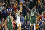 Utah Jazz forward Bojan Bogdanovic, center, shoots the winning basket in the final seconds, as Milwaukee Bucks forward Khris Middleton (22) defends during an NBA basketball game Friday, Nov. 8, 2019, in Salt Lake City. (AP Photo/Rick Bowmer)