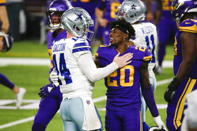 Dallas Cowboys quarterback Andy Dalton (14) talks with Minnesota Vikings cornerback Jeff Gladney (20) after an NFL football game, Sunday, Nov. 22, 2020, in Minneapolis. The Cowboys won 31-28. (AP Photo/Bruce Kluckhohn)