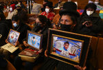 Women hold portraits of their relatives who died in confrontations with security forces, during a presentation of an Independent Human Rights Experts' report regarding the political crisis and violence of 2019 that led to the fall of President Evo Morales, in the Central Bank of Bolivia, in La Paz, Bolivia, Tuesday, Aug. 17, 2021. (AP Photo/Juan Karita)