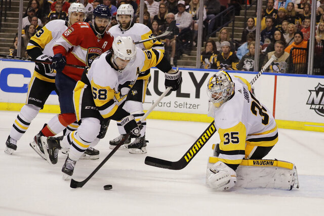 Pittsburgh Penguins defenseman Kris Letang (58) defends the goal against Florida Panthers center Vincent Trocheck (21) during the second period of an NHL hockey game, Saturday, Feb. 8, 2020, in Sunrise, Fla. (AP Photo/Brynn Anderson)
