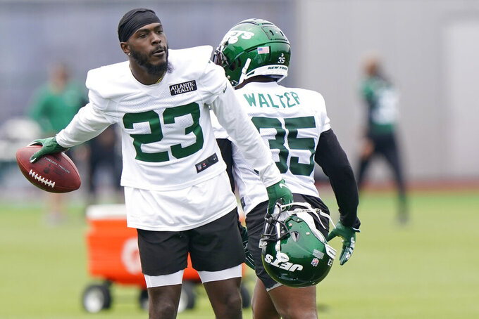 New York Jets running back Tevin Colman (23) tosses the football to an assistant after participating in running drills during an NFL football practice, Wednesday, June 2, 2021, in Florham Park, N.J. (AP Photo/Kathy Willens)