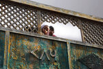 In this Tuesday, Dec. 24, 2019, photo, Muslim children look through broken fencing of their balcony in a congested neighborhood where five people died allegedly in police firing during protests against Citizenship Amendment Act, in Meerut, India. Tens of thousands of people have taken to the streets to oppose a new law that grants a path to citizenship for immigrants of every religion except Islam. Many say the law, passed by Prime Minister Narendra Modi's Hindu-nationalist government, discriminates against Muslims and undermines the country's secular foundations. (AP Photo/Rajesh Kumar Singh)