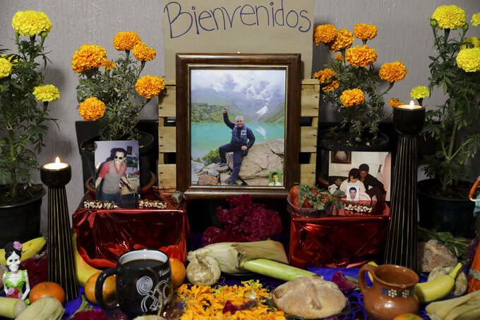 A portrait of Jose Valencia, a male nurse who died from symptoms related to COVID-19, placed on a Day of the Dead altar made by his daughter at their home in Mexico City, Sunday, Nov. 1, 2020. The weekend holiday isn't the same in a year so marked by death in a country where more than 90,000 people have died of COVID-19, many cremated rather than buried and with cemeteries forced to close. (AP Photo/Eduardo Verdugo)