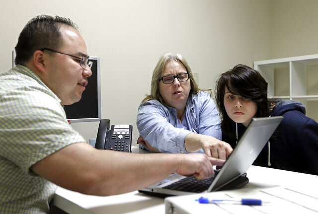 FILE - In this Feb. 12, 2015, file photo, enrollment counselor Vue Yang, left, goes over some of the health insurance plans available to Laura San Nicolas, center, accompanied by her daughter, Geena, 17, while looking for health insurance at Sacramento Covered in Sacramento, Calif. Nearly 1.6 million people have purchased health insurance through Covered California, state officials announced, Tuesday, Jan. 12, 2021. (AP Photo/Rich Pedroncelli, File)