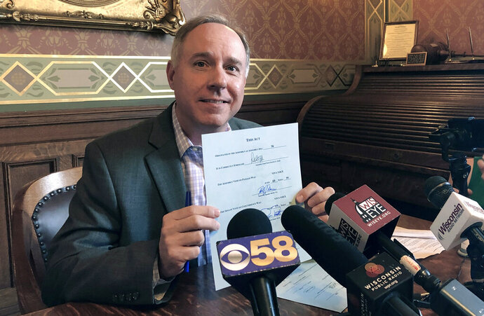 FILE - In this June 28, 2019, file photo, Wisconsin Assembly Speaker Robin Vos, left, shows off his signature on the state budget after signing the spending plan in his state Capitol office in Madison, Wis. Vos says he doesn't know if climate change is real, but it