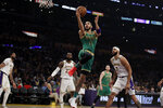 Boston Celtics' Jayson Tatum, center, drives to the basket past Los Angeles Lakers' JaVale McGee, right, during the first half of an NBA basketball game Sunday, Feb. 23, 2020, in Los Angeles. (AP Photo/Marcio Jose Sanchez)