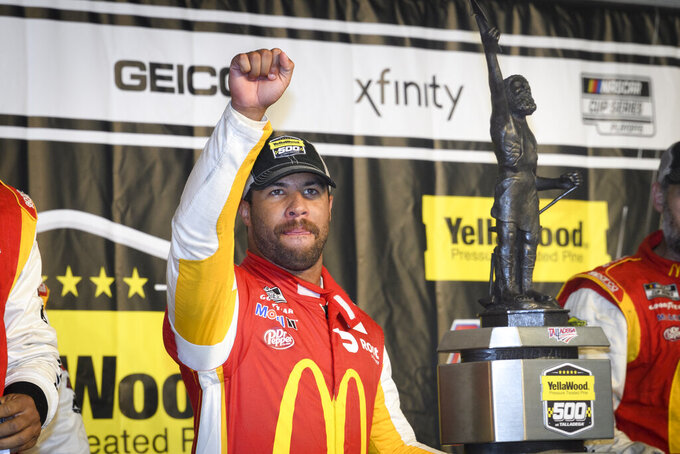 Bubba Wallace celebrates next to the trophy after winning a NASCAR Cup series auto race Monday, Oct. 4, 2021, in Talladega, Ala. The race was stopped mid-race due to rain. (AP Photo/John Amis)