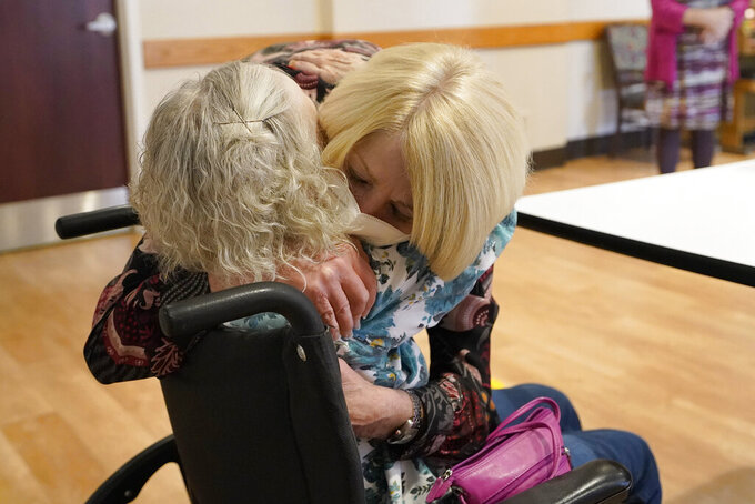 FILE - In this March 18, 2021, file photo, Mary Claire Lane, 86, left, a resident at Hellenic Nursing and Rehabilitation Center, in Canton, Mass., shares a hug with her daughter Anne Darling, of Attleboro, Mass., right, during a visit at the nursing home, in Canton. Nursing homes and other elderly residences battered by COVID-19 are easing lockdown-like restrictions more than a year into the pandemic. (AP Photo/Steven Senne, File)