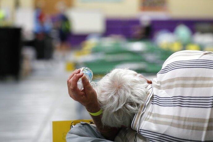 FILE - In this Sept. 1, 2019, file photo, an evacuee lies on a cot at an evacuation shelter for people with special needs, in preparation for Hurricane Dorian, at Dr. David L. Anderson Middle School in Stuart, Fla. Local officials across the South are still scurrying to fix their hurricane evacuation and sheltering plans because of changes needed due to coronavirus and a cratering economy. (AP Photo/Gerald Herbert, File)