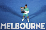 FILE- In this Feb. 21, 2021, file photo, Serbia's Novak Djokovic holds the Norman Brookes Challenge Cup after defeating Russia's Daniil Medvedev in the men's singles final at the Australian Open tennis championship in Melbourne, Australia. Djokovic is 26-0 in Grand Slam matches in 2021, moving him two victories away from being the first man to win all four major tennis championships in one season since Rod Laver in 1969. (AP Photo/Hamish Blair, File)