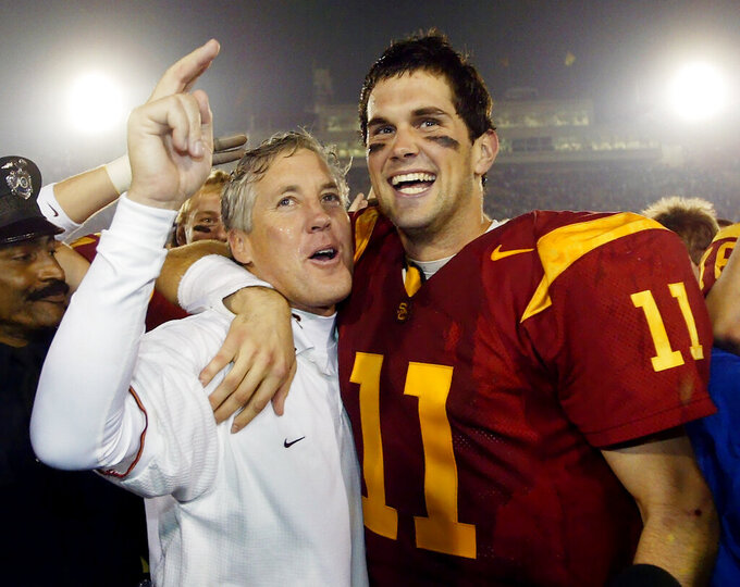 FILE - In this Dec. 6, 2003, file photo, Southern California quarterback Matt Leinart, right, hugs head coach Pete Carroll as they celebrate their win over Orgeon State, 52-28, in Los Angeles. In the 80-year history of The Associated Press college football poll, no team has had a longer uninterrupted run at No. 1 than coach Pete Carroll's Southern California Trojans. (AP Photo/Kevork Djansezian, File)