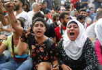 Anti-government protesters shout slogans as they block a main highway, in Beirut, Lebanon, Saturday, Oct. 26, 2019. Lebanese security forces pushed and dragged away protesters who refused to move from roadblocks in central Beirut on Saturday, to reopen roads closed during a campaign of civil disobedience. (AP Photo/Hussein Malla)