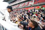Mercedes driver Lewis Hamilton, of Britain, left, celebrates with fans after winning the Spanish Formula One Grand Prix at the Barcelona Catalunya racetrack in Montmelo, Spain, Sunday, May 13, 2018. (AP Photo/Manu Fernandez)