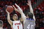Utah forward Timmy Allen (1) shoots as UC Davis guard Elijah Pepper (40) defends during the second half of an NCAA college basketball game Friday, Nov. 29, 2019, in Salt Lake City. (AP Photo/Rick Bowmer)
