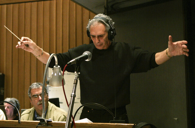 "FILE – In this Feb. 21, 2005, file photo, composer and conductor Bill Conti, music director of the 77th Academy Awards, conducts the show's orchestra during a rehearsal at Capitol Recording Studios in Los Angeles. Conti, the Oscar- and Emmy Award-winning composer who wrote scores for movies including ""Rocky,"" ""The Right Stuff"" and ""The Karate Kid"" is giving them to Louisiana State University. Conti, who grew up in Miami, went to LSU on a bassoon scholarship. The William and Shelby Conti Papers are expected to arrive sometime in the fall.  (AP Photo/Kevork Djansezian, File)"