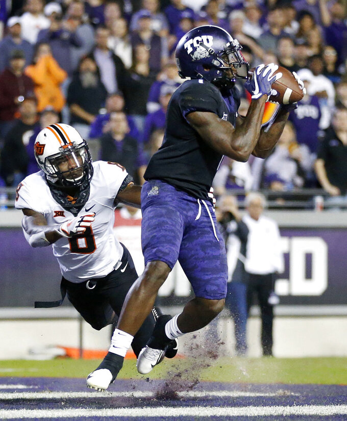 TCU wide receiver Jalen Reagor (1) pulls in a second-quarter touchdown reception in the end zone as Oklahoma State cornerback Rodarius Williams (8) defends during an NCAA college football game in Fort Worth, Texas, Saturday, Nov. 24, 2018. (Tom Fox/The Dallas Morning News via AP)