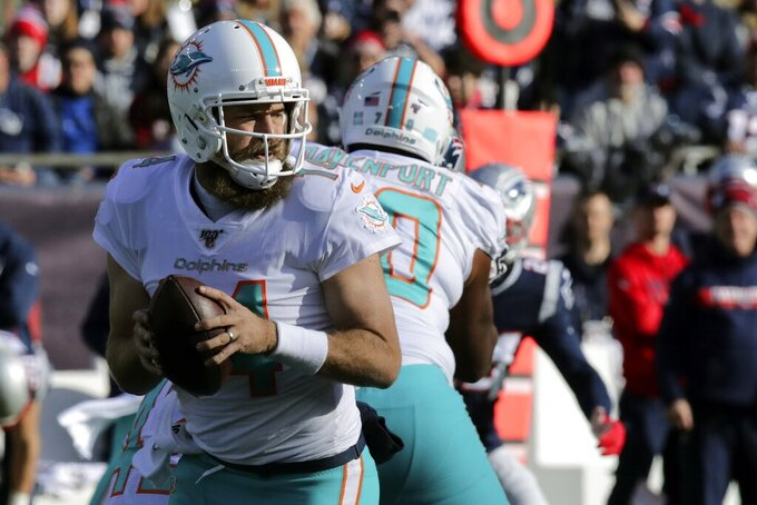 Miami Dolphins quarterback Ryan Fitzpatrick rolls out to pass against the New England Patriots in the first half of an NFL football game, Sunday, Dec. 29, 2019, in Foxborough, Mass. (AP Photo/Charles Krupa)