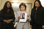 As Latresa Scaff, right, and Rochelle Washington, left, look on as attorney Gloria Allred holds up a picture of them as teenagers on the night they claim they became victims of musician R. Kelly's sexual advances during a news conference in New York, Thursday, Feb. 21, 2019. Scaff and Washington are accusing musician R. Kelly of sexual misconduct on the night they attended a concert of his while they were teenagers.(AP Photo/Seth Wenig)