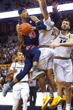 Auburn's Samir Doughty, left, shoots past Missouri's Dru Smith, center, and Reed Nikko, right, during the first half of an NCAA college basketball game Saturday, Feb. 15, 2020, in Columbia, Mo. (AP Photo/L.G. Patterson)
