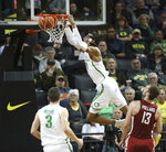 Oregon's Kenny Wooten, top, dunks over teammate Payton Pritchard, left and Washington State's Jeff Pollard, right, during the second half of an NCAA college basketball game Sunday, Jan 27, 2019, in Eugene, Ore. (AP Photo/Chris Pietsch)
