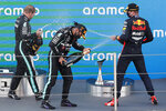 Winner Mercedes driver Lewis Hamilton of Britain, center, celebrates on the podium besides second placed Red Bull driver Max Verstappen of the Netherlands, right, and third placed Mercedes driver Valtteri Bottas of Finland after the Formula One Grand Prix at the Barcelona Catalunya racetrack in Montmelo, Spain, Sunday, Aug. 16, 2020. (Alejandro Garcia, Pool via AP)