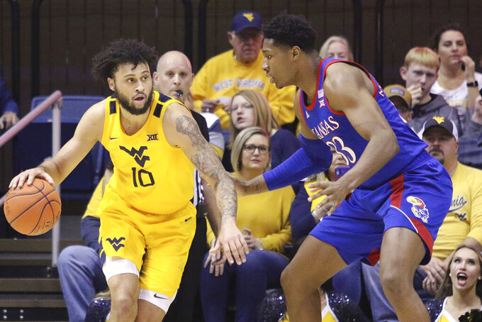 West Virginia guard Jermaine Haley (10) is defended by Kansas forward David McCormack (33) during the first half of an NCAA college basketball game Wednesday, Feb. 12, 2020, in Morgantown, W.Va. (AP Photo/Kathleen Batten)