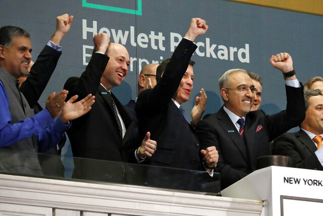 FILE - In this Wednesday, Oct. 24, 2018, file photo, Hewlett Packard Enterprise President & CEO Antonio Neri, right, rings the New York Stock Exchange opening bell. Tech giant Hewlett Packard Enterprise said it is moving its global headquarters to the Houston area from California. Texas Gov. Greg Abbott's office announced Tuesday, Dec. 1, 2020, that the relocation will increase the company's presence in the area, which is already home to more than 2,600 employees. (AP Photo/Richard Drew, File)