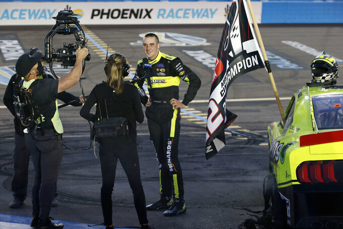 Austin Cindric, center, gives an interview after winning the NASCAR Xfinity Series auto race at Phoenix Raceway, Saturday, Nov. 7, 2020, in Avondale, Ariz. (AP Photo/Ralph Freso)