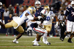 Arizona wide receiver Stanley Berryhill III (1) is tackled by UCLA defensive back Qwuantrezz Knight (24) during the first half of an NCAA college football game Saturday, Oct. 9, 2021, in Tucson, Ariz. (AP Photo/Chris Coduto)