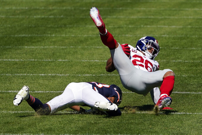 New York Giants running back Saquon Barkley (26) is brought down by Chicago Bears cornerback Kyle Fuller (23) during the first half of an NFL football game in Chicago, Sunday, Sept. 20, 2020. (AP Photo/Charles Rex Arbogast)