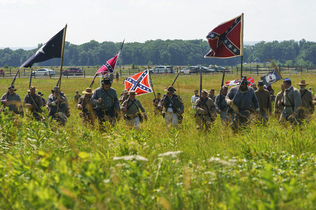 FILE - In this Friday, July 3, 2020, file photo, Civil War reenactors marching with Confederate battle flags during their reenactment of Pickett's Charge at Gettysburg National Military Park in Gettysburg, Pa. The banner, with its red field and blue X design, is the best known of the flags of the Confederacy, but the short-lived rebel nation also had other flags. (AP Photo/Carolyn Kaster, File)