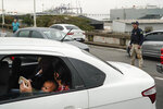 A woman sits in a car with a baby as they wait on a blocked access as a Federal Highway Police officer stands next at the busy bridge connecting the city of Niteroi to Rio de Janeiro , Brazil, Tuesday, Aug. 20, 2019 during a hostage standoff.   An armed man holding dozens of people hostage on a public bus and threatening to set the vehicle on fire was seized by police after a four-hour long standoff, Brazilian police said.  (AP Photo/Leo Correa)